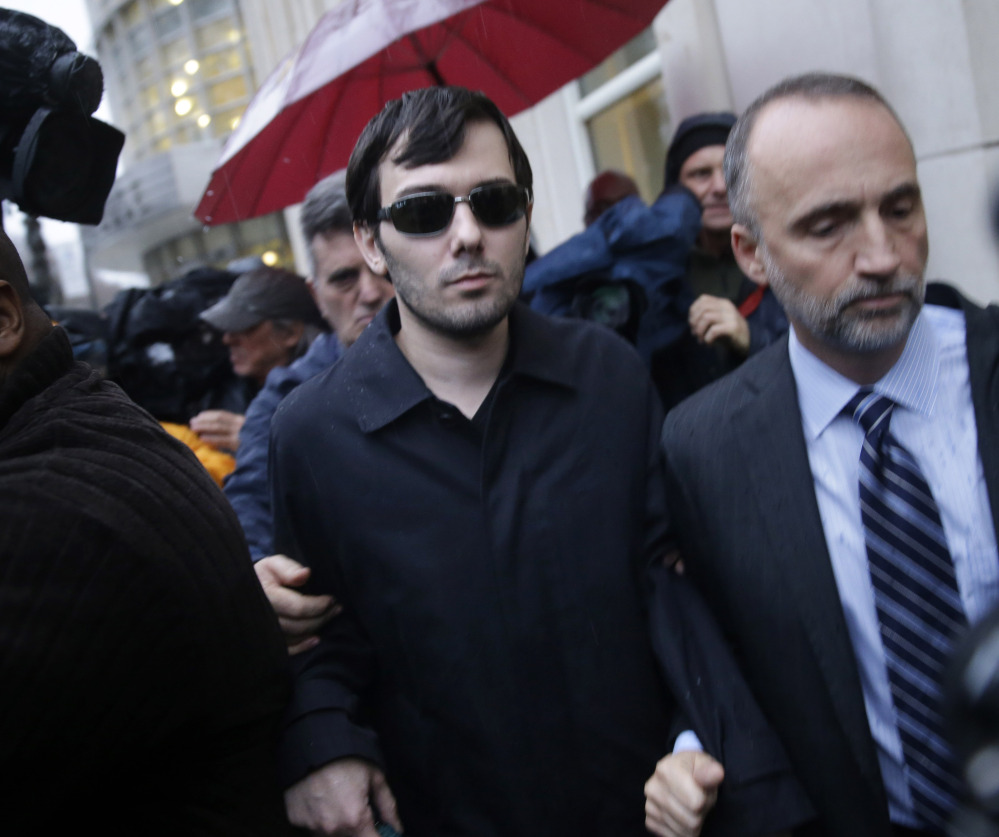 Martin Shkreli, center, leaves the courthouse after his arraignment in New York, Thursday, Dec. 17, 2015. Shkreli, the former hedge fund manager vilified in nearly every corner of America for buying a pharmaceutical company and jacking up the price of a life-saving drug more than fiftyfold, was arrested Thursday on securities fraud charges unrelated to the furor. (AP Photo/Seth Wenig)