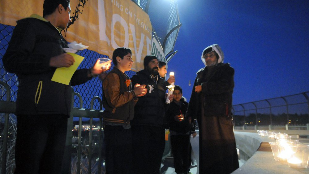 Members of a variety of faiths gather Wednesday to light candles and stand together in a show of support on Memorial Bridge in Augusta.