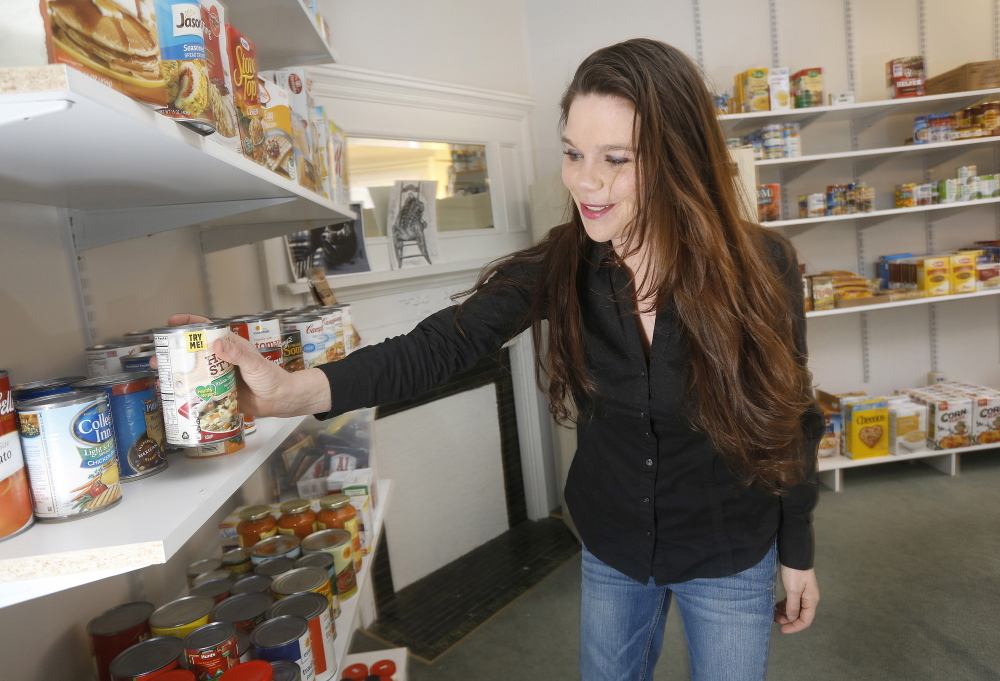 Leanna Shields organizes shelves at the Captain's Cupboard Food Pantry on the Southern Maine Community College campus in South Portland. Food banks across the state would benefit if every Shaw's in Maine could donate near-expired food, a reader says.