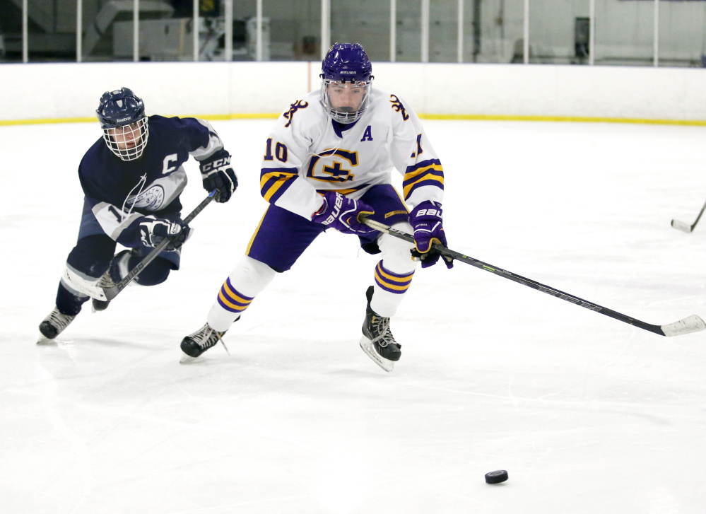 Patrick Grant, left, of Yarmouth and Garett Dion of Cheverus battle for the puck. Grant finished with a goal and two assists.