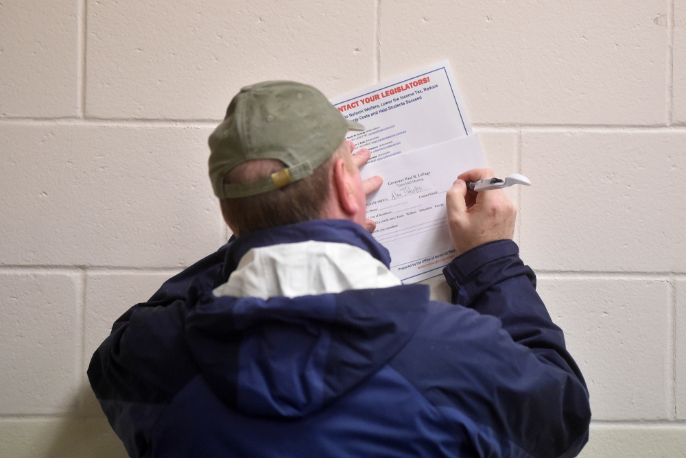 A member of the community fills out a question form for Gov. Paul LePage during a town hall meeting Thursday at Waterville Junior High School.