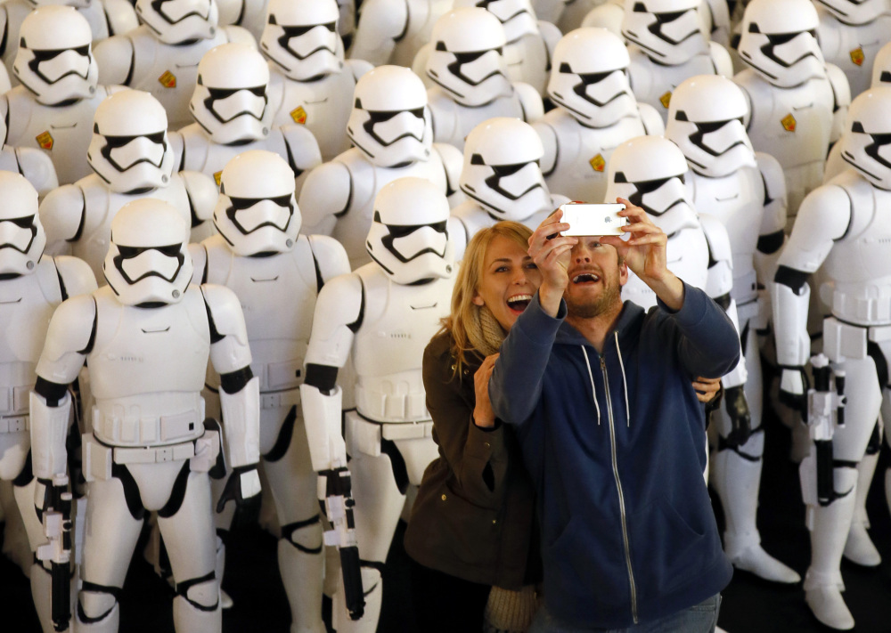 A couple takes a selfie together in front of over 100 JAKKS BIG-FIGS Stormtrooper action figures as part of an installation at The Americana at Brand for the opening of Star Wars: The Force Awakens in Glendale, Calif.