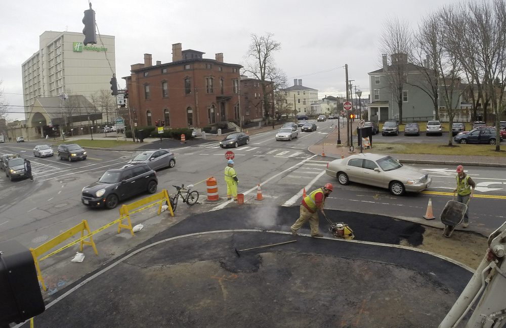 Workers on Friday shave back the sidewalk bump-out on Spring Street in Portland that prompted criticism from some West End residents.