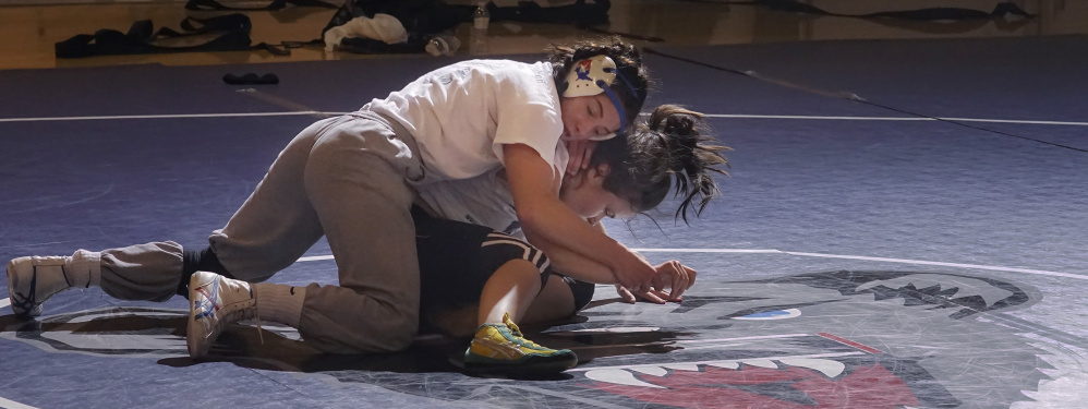 Nursing drew Samantha Frank, top, to Orono, and while she's still pursuing it as a career, she also finds fullfillment with the school's club wrestling program, as does Leticia Souza, who's going to need some kind of move to escape this hold.