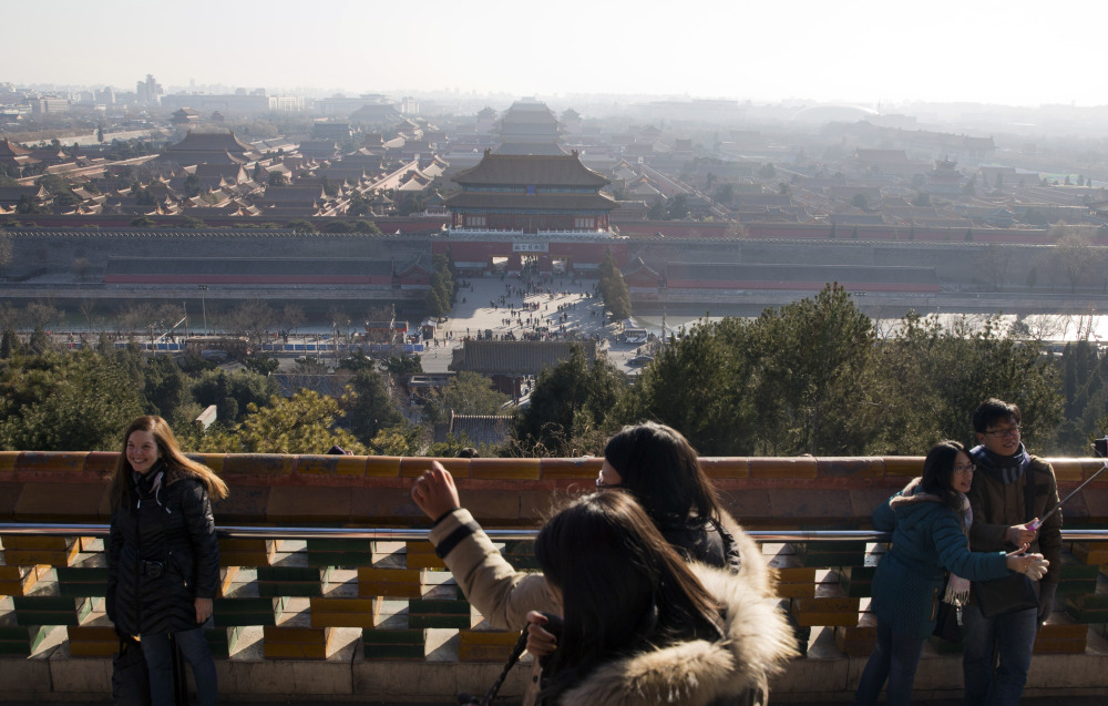 Visitors take photos from a pavilion overlooking the Forbidden City in Beijing on Friday. A wave of smog is predicted to settle over the city from Saturday to Tuesday.