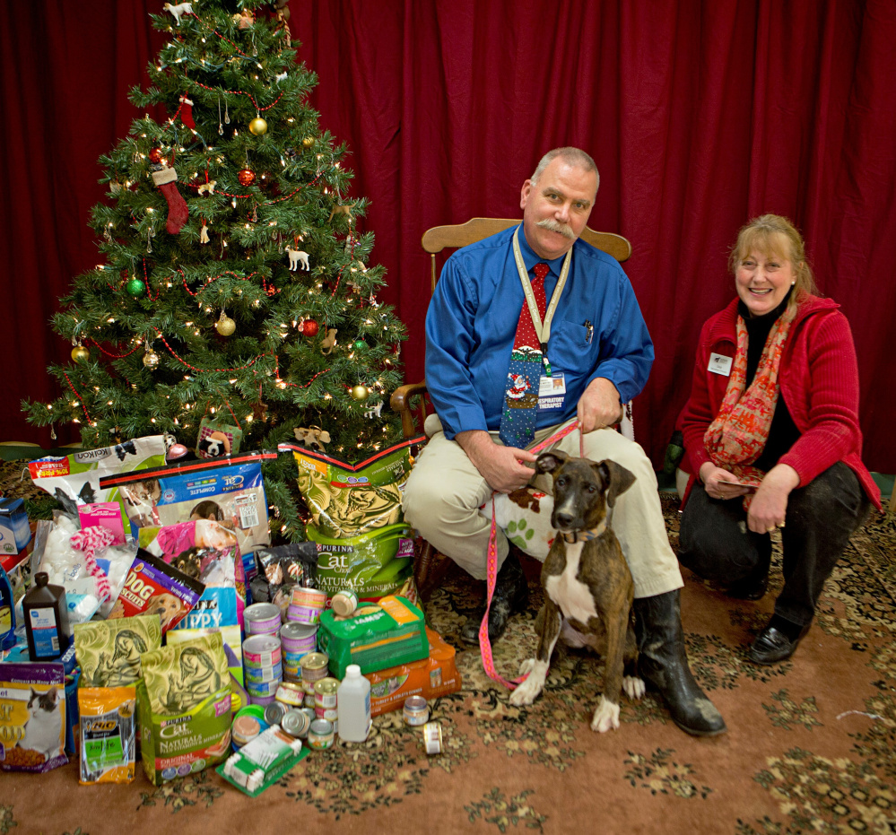 Howard Mette, a department director at Inland Hospital, poses in front of the gifts donated by hospital workers to the Humane Society Waterville Area animal shelter. With Mette are Paisley, a shelter resident, and the shelter's director, Lisa Smith.