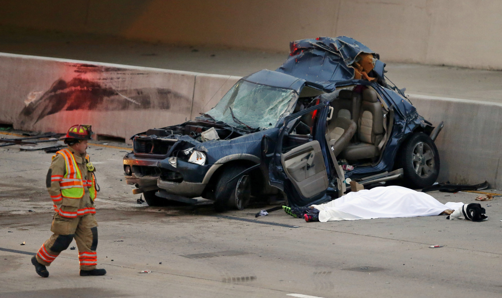 An Arlington firefighter inspects an SUV that was hit by a Greyhound bus in the fast lane on westbound Interstate 30 near Collins St. in Arlington, Texas, killing one, under sheet, in the vehicle early Sunday.