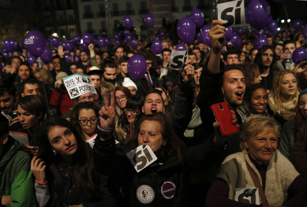 Supporters of the Podemos party wait for official results in Madrid on Sunday.