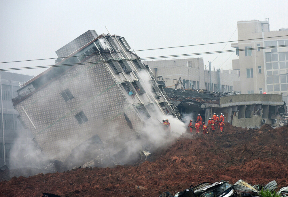 Rescuers cluster near a collapsed building as they search for survivors Sunday after a landslide in Shenzhen, a city in south China's Guangdong province.