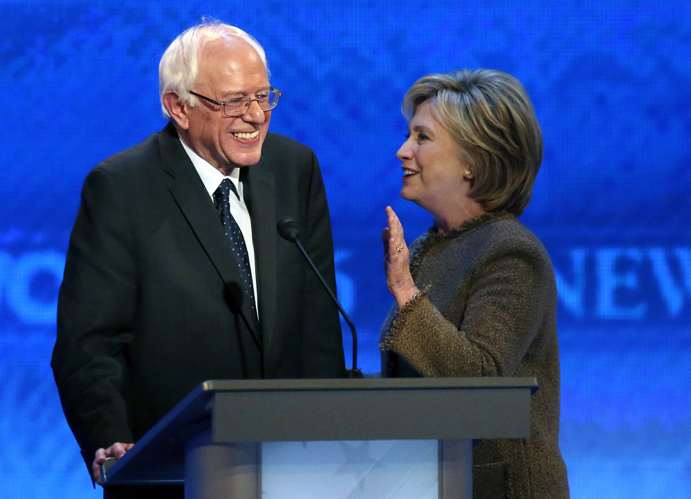 Bernie Sanders talks with Hillary Clinton during a break at the Democratic presidential primary debate Saturday at Saint Anselm College in Manchester, N.H.