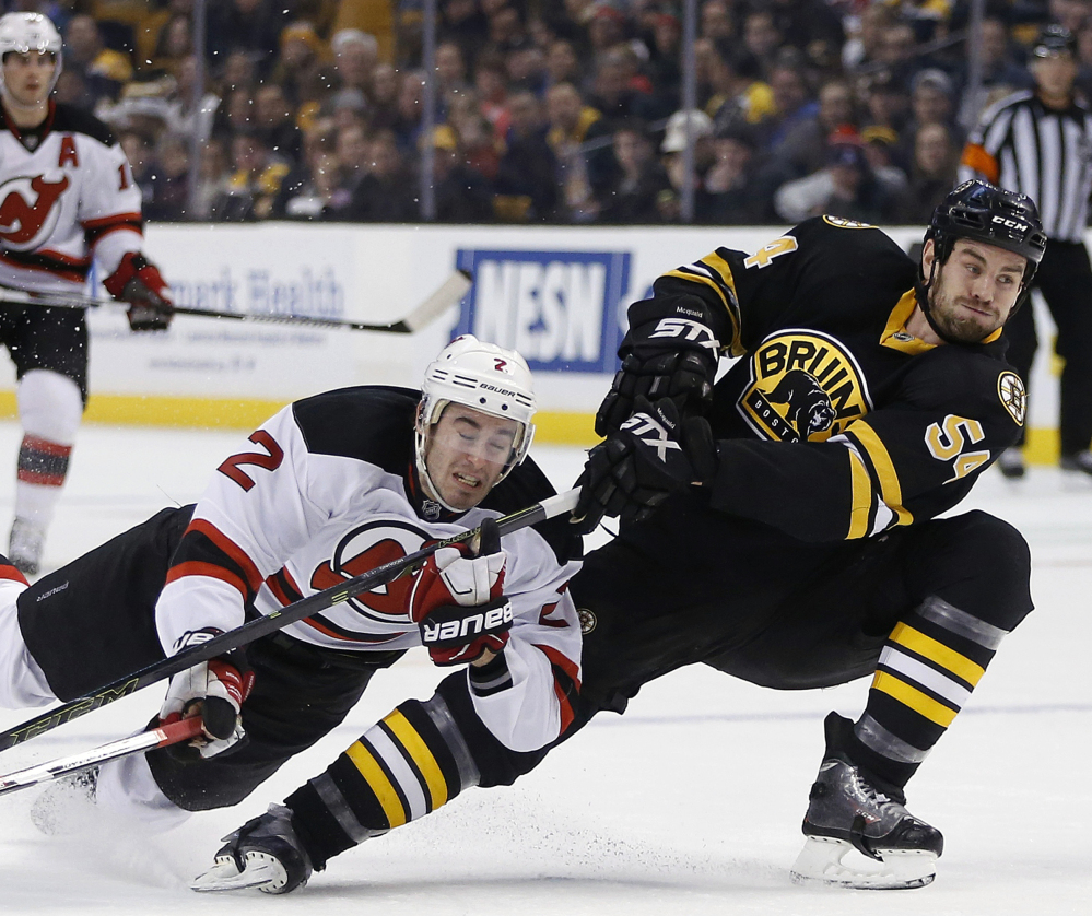 New Jersey's John Moore, left, gets tangled up with Boston's Adam McQuaid during their game Sunday in Boston. The Bruins scored in the first period, then beat the Devils in a shootout and are 11-1-3 in their last 15 games.