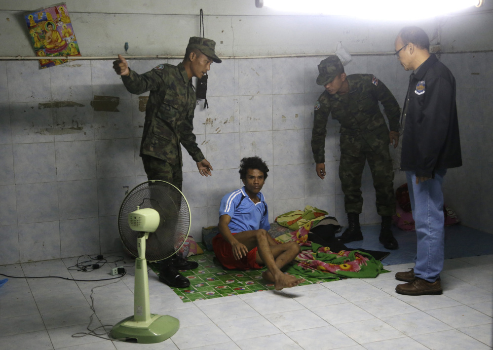 In this Monday, Nov. 9, 2015 photo, Thai soldiers and a member of the Department of Special Investigation wake up a worker during a raid on a shrimp shed in Samut Sakhon, Thailand.