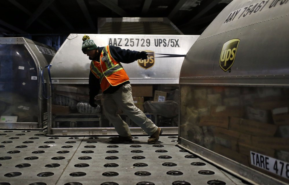 A UPS worker pulls a container full of packages across a floor embedded with casters at Worldport in Louisville, Ky. UPS will deliver 36 million packages Tuesday.