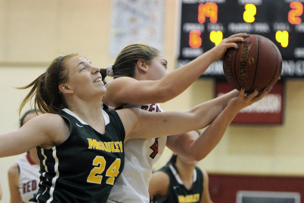 Emily Weisser of McAuley, left, battle for a rebound with Brooke Malone of Scarborough during Tuesday night's game in Scarborough.