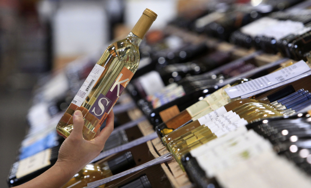 A shopper holds up a bottle of wine from a large selection at a Costco warehouse store Tuesday, Aug. 24, 2010, in Seattle. The cavernous stores in Costco's home state lack something you can find in its warehouses in California, Alaska and dozens of other states: jumbo-sized bottle of Maker's Mark, Absolut vodka and other popular brands of hard liquor. Two ballot measures on the November ballot would largely sweep away the state's post-Prohibition restrictions on alcohol, and perhaps herald a broader push to bring booze into the big box stores in the roughly 20 states that still keep a tight lid on the hard stuff. (AP Photo/Elaine Thompson)