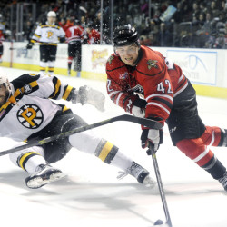 Kyle Rau of Portland, right, tries to get past Tommy Cross of Providence during the second period of Tuesday night's game at the Cross Insurance Arena in Portland. The Pirates won the game, 4-2.