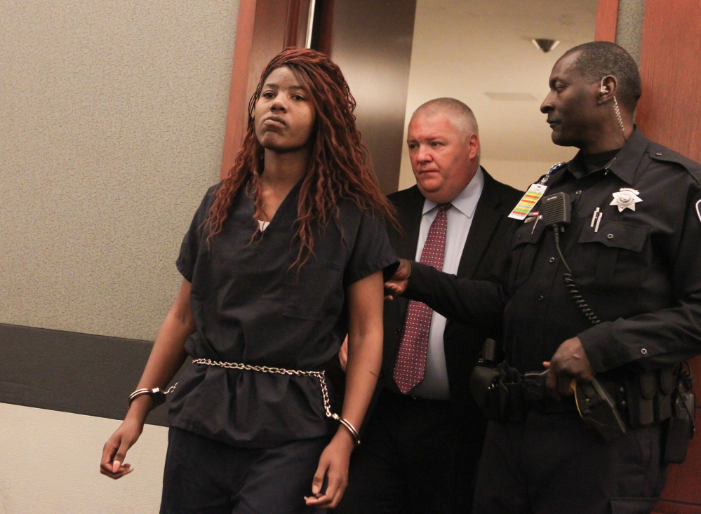 Lakeisha Nicole Holloway enters district court with one of her public defenders, Scott Coffee, for her arraignment Wednesday in Las Vegas. Holloway, who crashed her car into pedestrians on the Las Vegas Strip on Sunday, has been charged with murder, child abuse and hit-and-run.