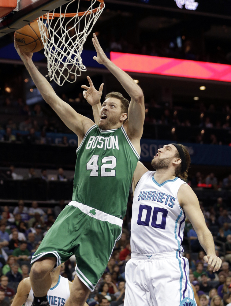The Celtics' David Lee drives past Charlotte's Spencer Hawes in the first half. Lee finished with 10 points in the game.