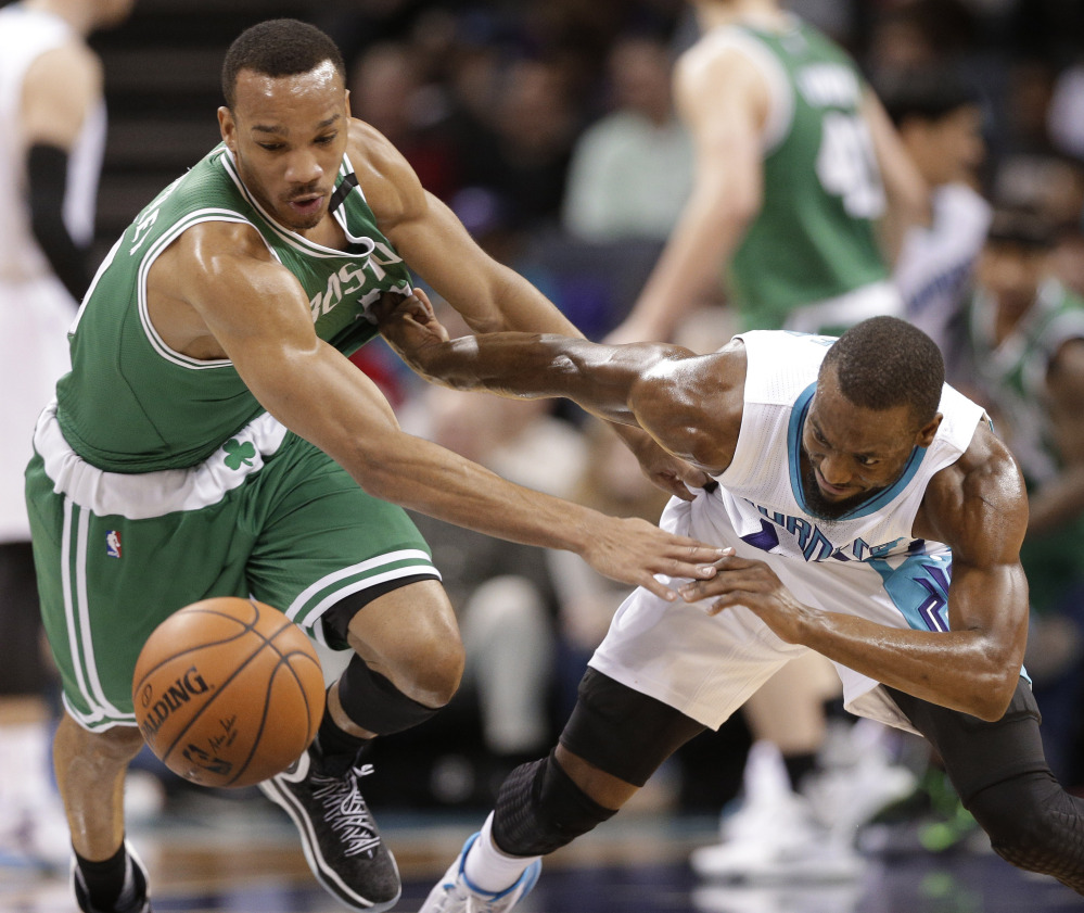 The Charlotte Hornets' Kemba Walker and the Celtics' Avery Bradley chase the ball in the first half of Boston's win Wednesday night in Charlotte. Bradley scored 18 points for the Celtics.