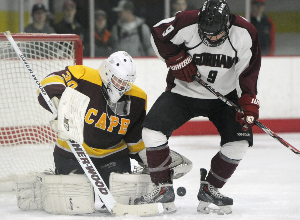 Cape Elizabeth goalie Grant Rusk holds his ground Wednesday as Holden Edwards of Gorham attempts to redirect a shot into the net. Cape Elizabeth won, 5-1.