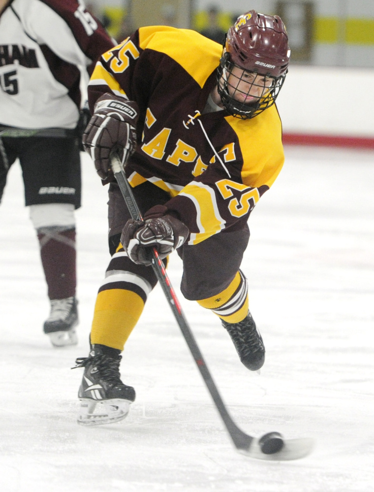Eli Babcock of Cape Elizabeth keeps his eyes on the puck while sending a shot on goal. Babcock finished with two assists against Gorham.