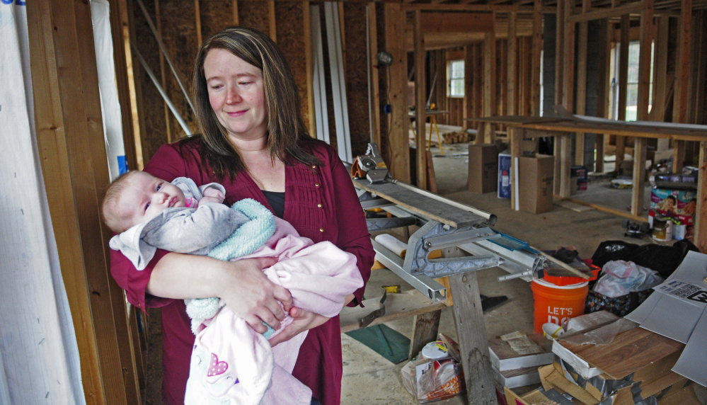 Missy Peasley holds daughter Brooke as she talks about her family's new home that's under construction in Somerville.