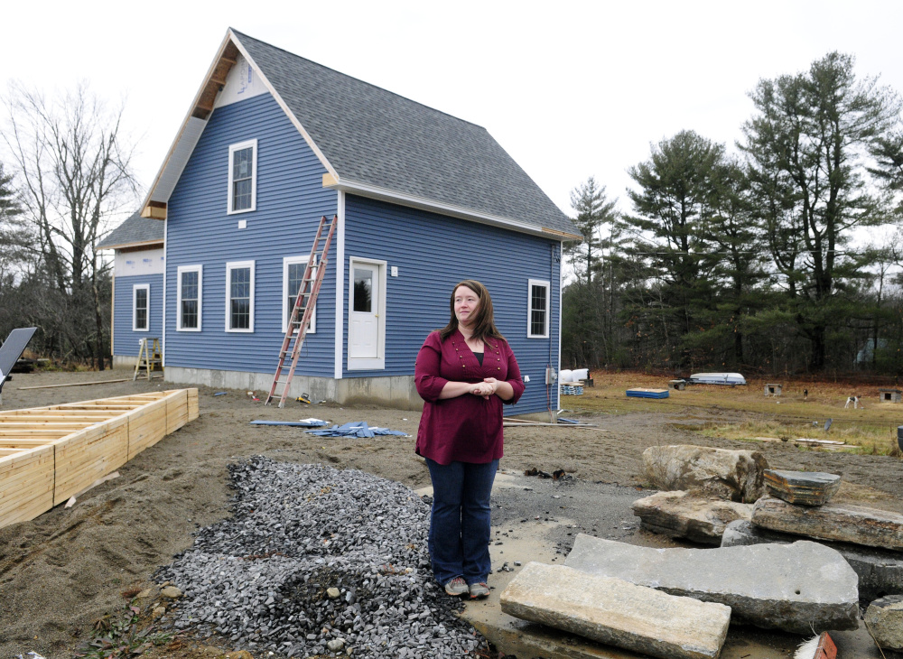 Missy Peasley stands on the site of her family's home that burned down and in front of her family's new home on Dec. 18 in Somerville.