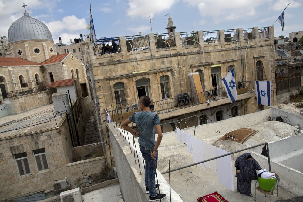 A Palestinian woman takes down laundry on her balcony facing a Jewish seminary in Jerusalem's Old City Muslim Quarters. Jews can't afford to be a minority in Israel by allowing a full right of return to refugees, a reader says.