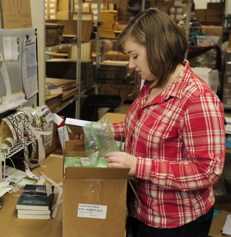 Shannon Butler, office manager for Islandport Press in Yarmouth, puts recycled packaging from Gulf of Maine Books into one of the boxes of books she is shipping to a customer.