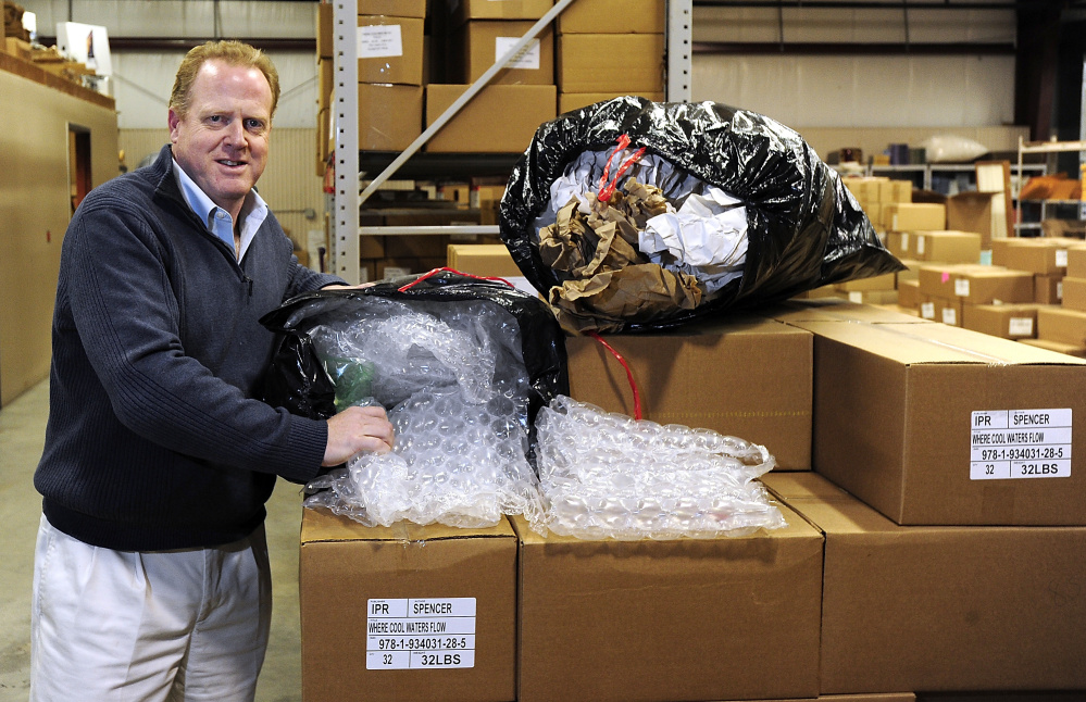 Dean Lunt, owner of Islandport Press, shows the bags of recycled packaging from Gulf of Maine Books that they will use in packing their books for shipping.  Gordon Chibroski/Staff Photographer