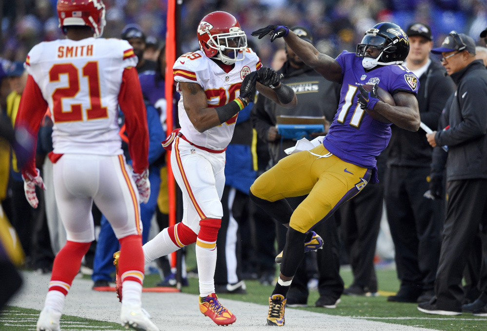 Kansas City Chiefs free safety Eric Berry, center, pushes Baltimore Ravens wide receiver Kamar Aiken out of bounds as teammate Sean Smith (21) watches in the first half on Dec. 20 in Baltimore. The Associated Press
