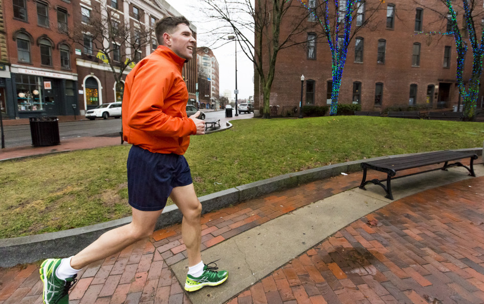 John Marshall, a holiday visitor from Salem, New Hampshire, jogs in a pair of shorts on Dec. 24 past the holiday lights on Exchange Street in Portland.
