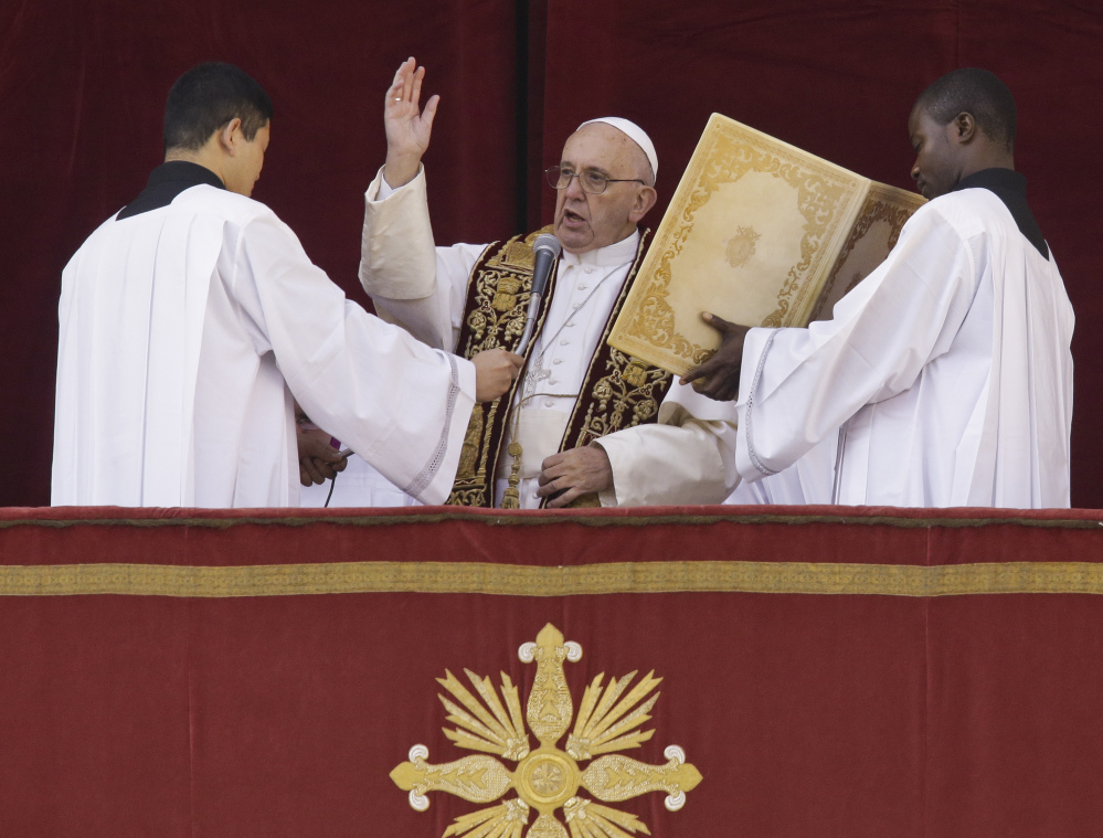 "Pope Francis delivers his ""Urbi et Orbi"" (to the city and to the world) blessing from the central balcony of St. Peter's Basilica at the Vatican on Friday."