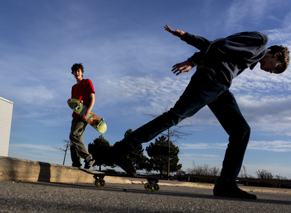 Aidan Parker looks on as his brother Julian Parker skates at Portland's Ocean Gateway Terminal on Christmas Day, the warmest Christmas on record in Portland. Gabe Souza/Staff Photographer