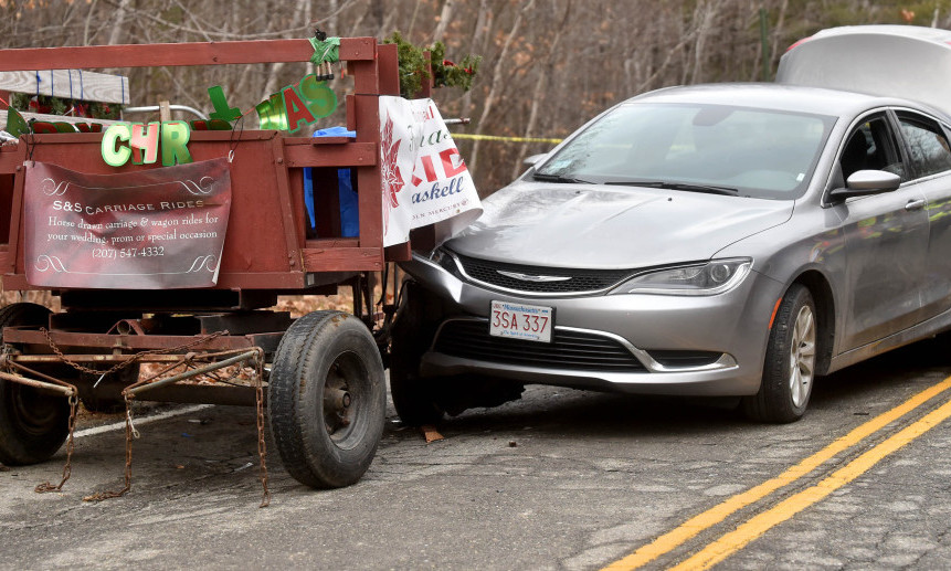 Responders tend to victims after a car crashed into a horse-drawn carriage Friday on Industrial Street in Waterville. Six people were treated at hospitals  and released. One person was flown by a LifeFlight helicopter to a Portland hospital.