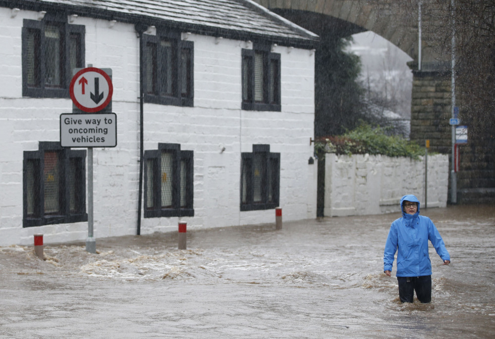 A person wades through flood water at Mytholmroyd in Calderdale, West Yorkshire, on Saturday. Parts of northwest England already hit hard by flooding in recent weeks were under severe flood warnings Saturday because of forecasts for more heavy rain, with some areas being evacuated.