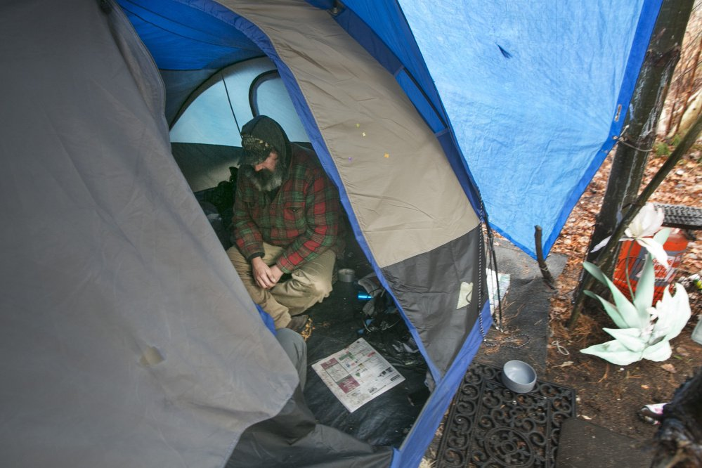 A homeless man shelters in a tent on the outskirts of Portland to get out of the rain Dec. 17. Two readers are troubled by the influx of homeless camps along land trust trails.