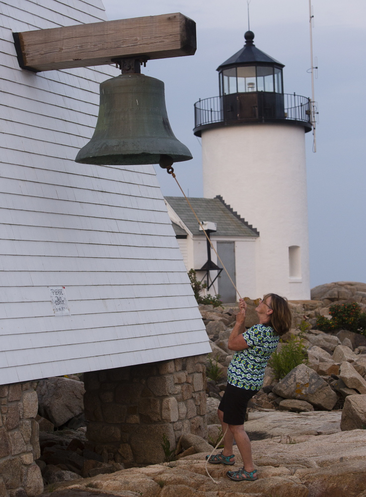 Lee Maynard, a Kennebunkport Conservation Trust volunteer, rings the ceremonial bell at sunset after doing work to maintain one of the trust's properties. The trust has protected 2,400 acres and 15 miles of a forest trail over 40 years.