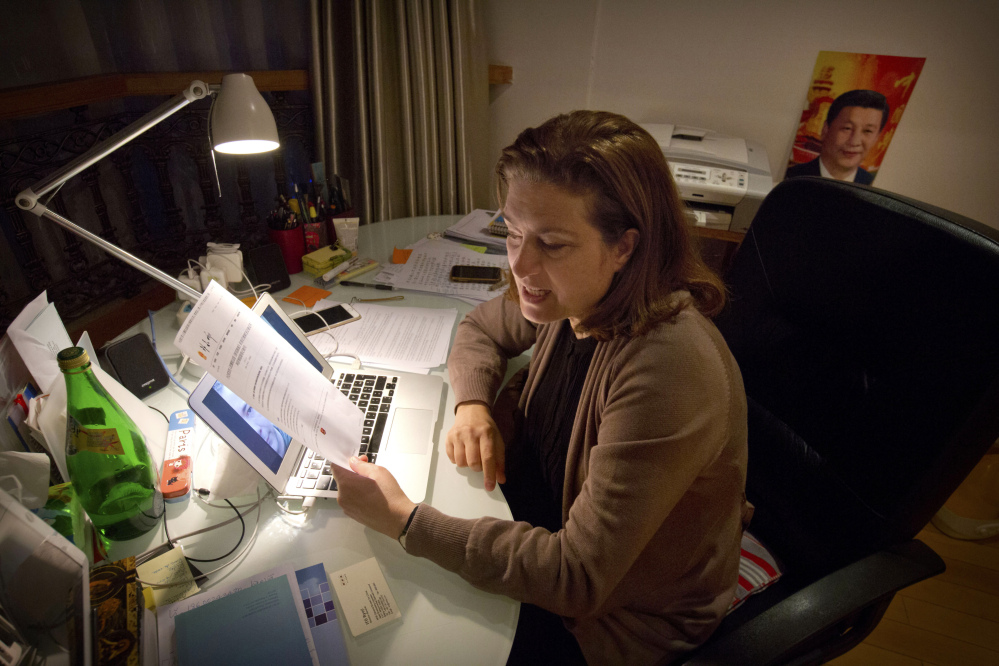 French journalist Ursula Gauthier, a reporter for the French news magazine L'Obs, holds a statement criticizing her from the Chinese Ministry of Foreign Affairs as she sits at her desk in her apartment in Beijing, Saturday. China said it will not renew press credentials for Gauthier, effectively expelling her. The Associated Press