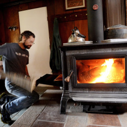 Steve Fuller of Peru feeds his new Equinox wood stove. He and his wife, Marcia, are among the first Mainers to receive $1,000 for replacing an older burner with one certified by the EPA.