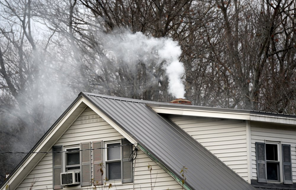 Smoke wafts from a chimney at a home in Livermore, one of 10 Androscoggin River valley communities where homeowners are eligible for a wood stove change-out program that provides a $1,000 voucher for replacing older burners with stoves that are approved by the Environmental Protection Agency. Shawn Patrick Ouellette/Staff Photographer