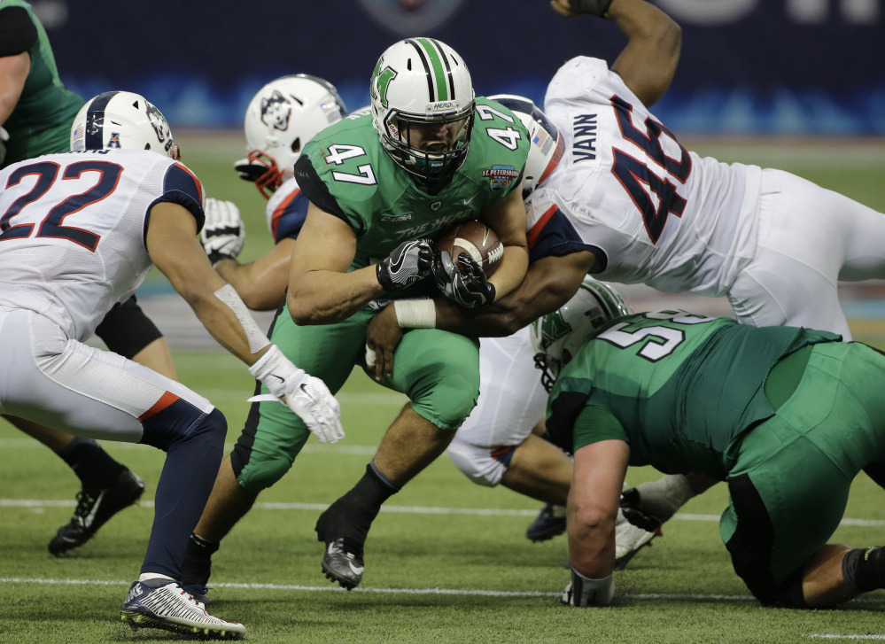 Devon Johnson of Marshall sprints through the Connecticut line during their St. Petersburg Bowl game in Florida. Marshall came away with a 16-10 victory and finished with a 10-3 record.