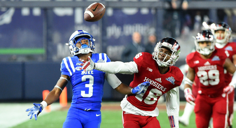 Rashard Fant of Indiana, center, breaks up a pass intended for T.J. Rahming of Duke during the second quarter of Duke's 44-41 overtime victory Saturday in the Pinstripe Bowl at Yankee Stadium.