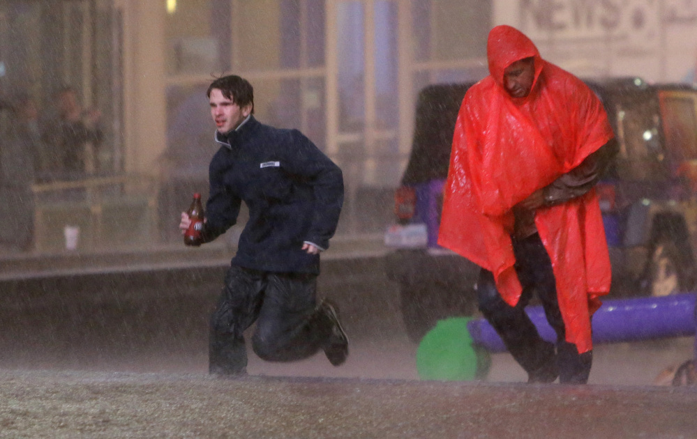 People run as weather sirens sound as a severe storm passes over downtown Dallas on Saturday.