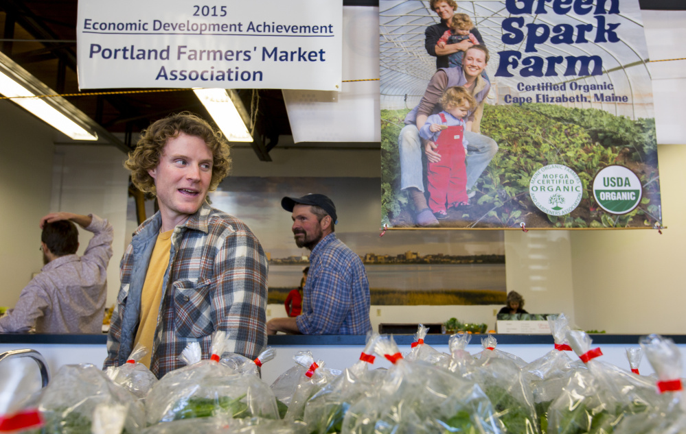 Austin Chadd, owner of Green Spark Farm of Cape Elizabeth, awaits customers at the farmers market.