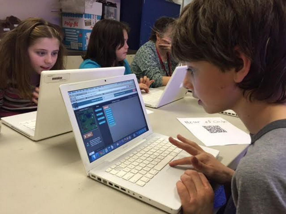 "Ryan Chase, right, Tabitha Boudle, left, and Kelci Nguyen, students at the Wells-Ogunquit Community School District, participate in a computer programming session called ""Hour of Code.""  The program was held in conjunction with Computer Science Education Week."