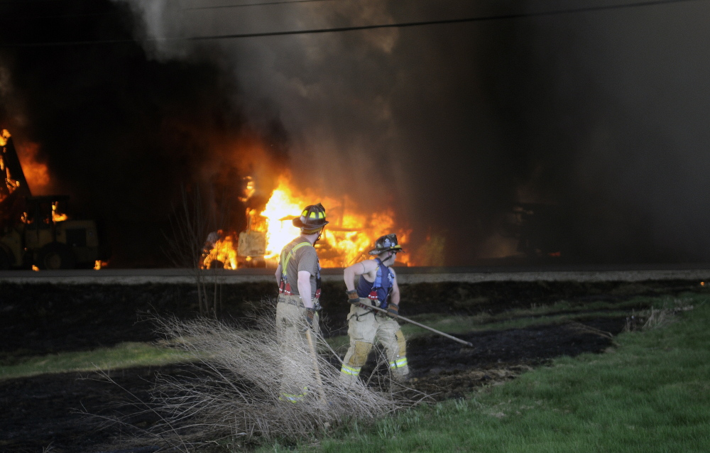 Firefighters extinguish a brush fire from an explosive blaze that destroyed AD Electric Inc.'s warehouse in Monmouth in May. The original $21,600 fine was reduced on appeal.