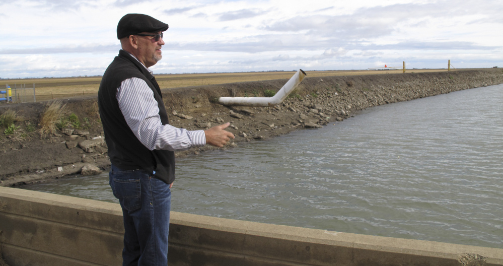Chris White, general manager of the Central California Irrigation District, explains the expense – which has already soared into the millions of dollars in his district – of fixing infrastructure damaged by the sinking of land near Dos Palos, Calif.