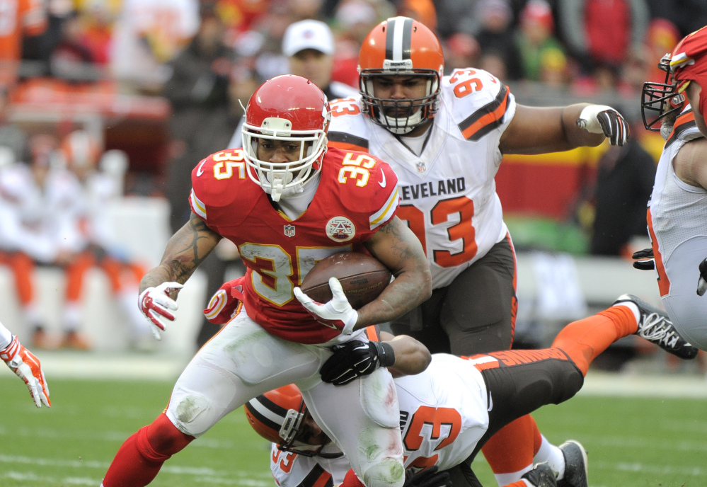 Chiefs running back Charcandrick West runs away from Cleveland's John Hughes, bottom, and Craig Robertson as Kansas City clinched a playoff spot with a 17-13 win Sunday.