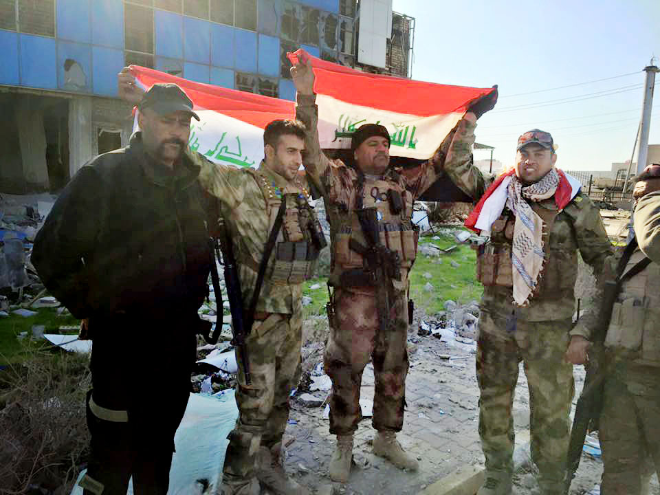 Iraqi soldiers hold national flags in the government complex in central Ramadi on Monday after retaking the strategic site from Islamic State militants who have occupied the city since May.